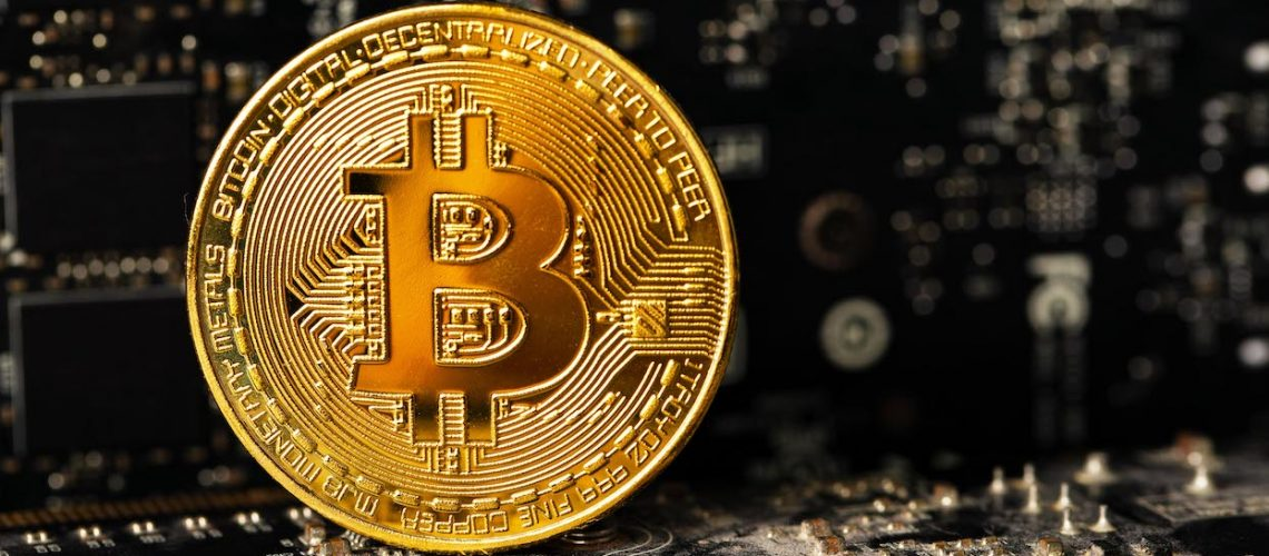 Close-up of a dark gold bitcoin on crypto mining GPU circuit board computer hardware. Virtual money or blockchain cryptocurrency.