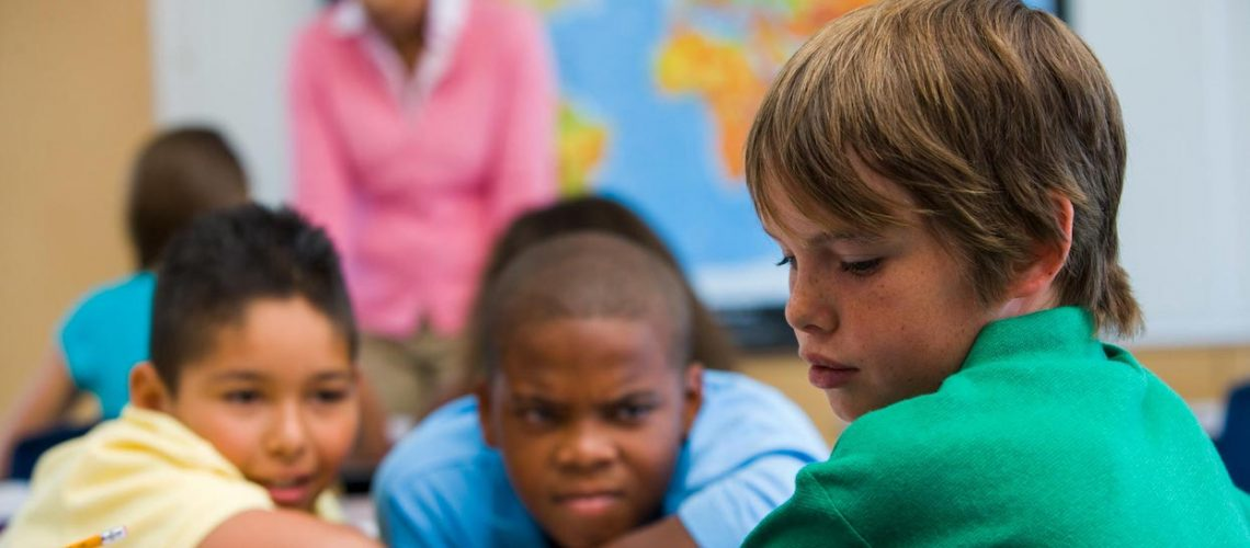 Boy being bullied in elementary school classroom