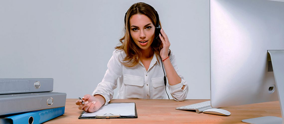 Young concentrated woman in headphones and microphone talking with client while sitting at the office desk over white background