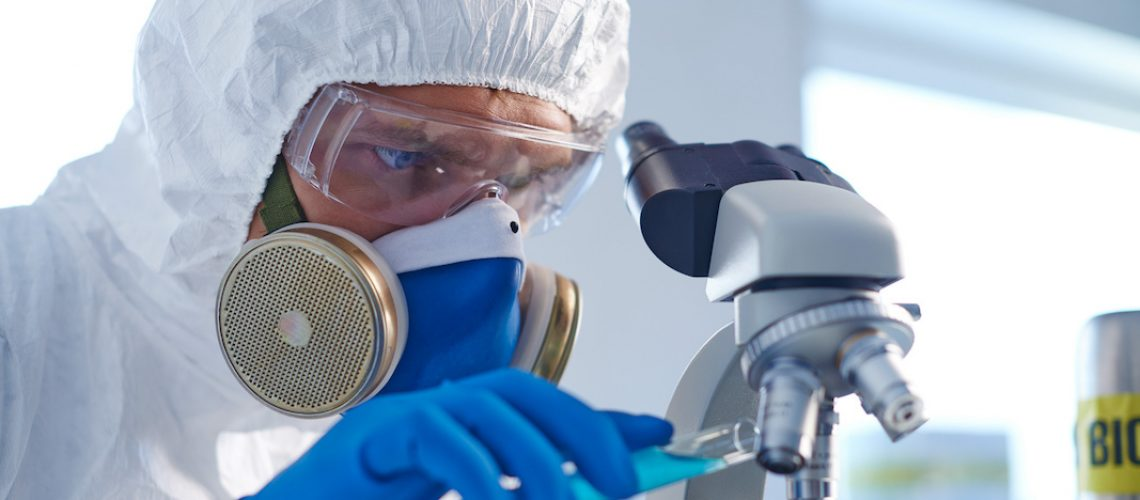 Male chemist in protective clothing studying new fluid in lab