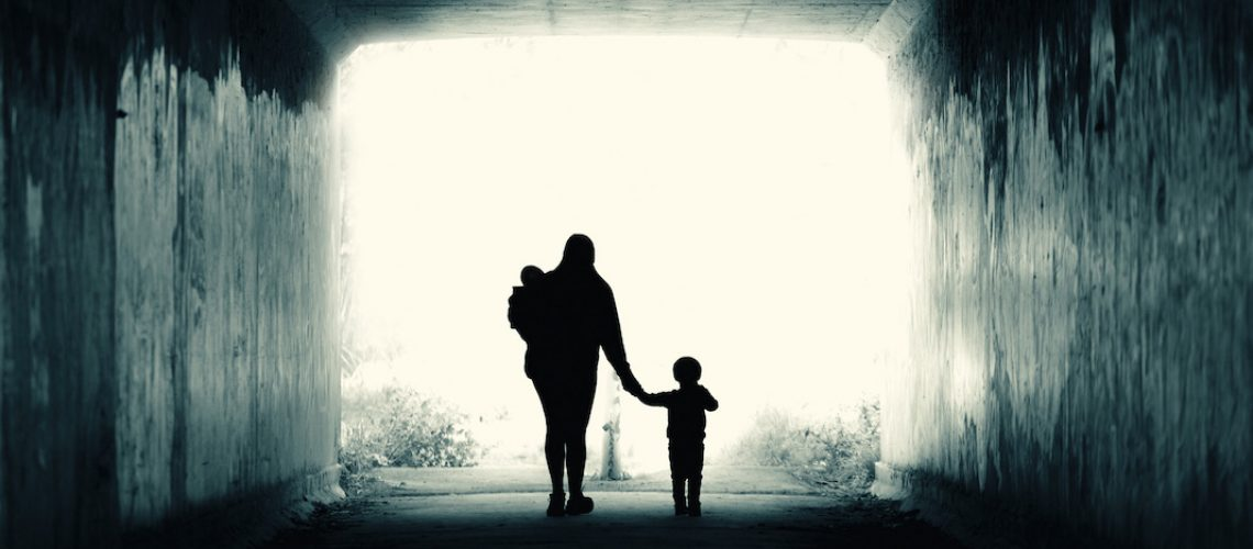 A single mother and two children walk into the light