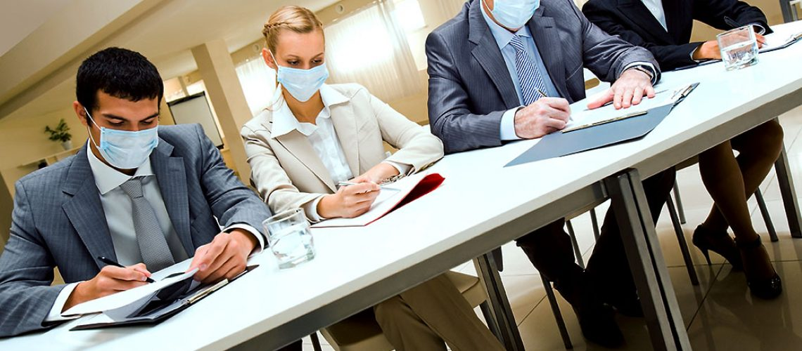 Portrait of group of business partners in protective masks during work